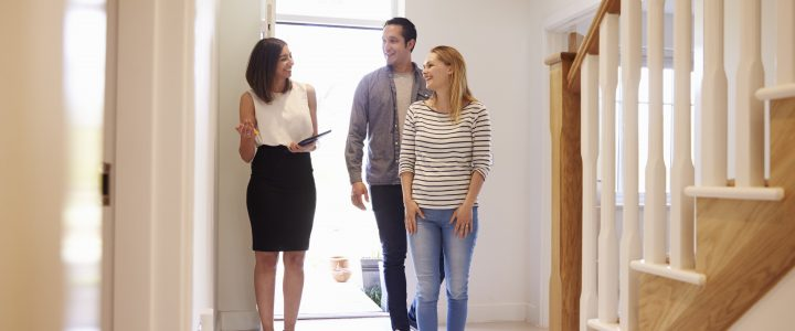 A real estate agent showing a house to a couple