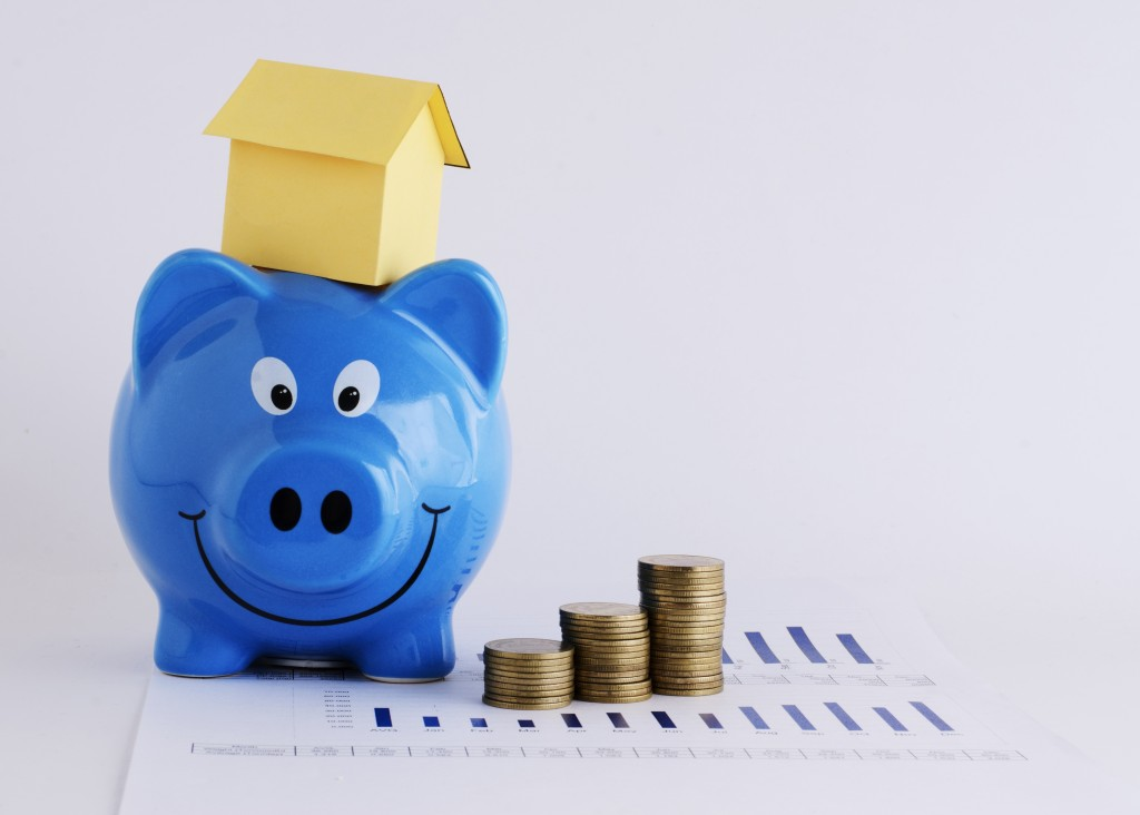 House model on top of piggy bank and coins