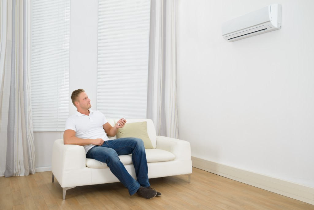 Man siting on sofa with air conditioner