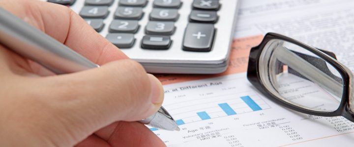 Business brokerage with calculator, pen and eyeglasses