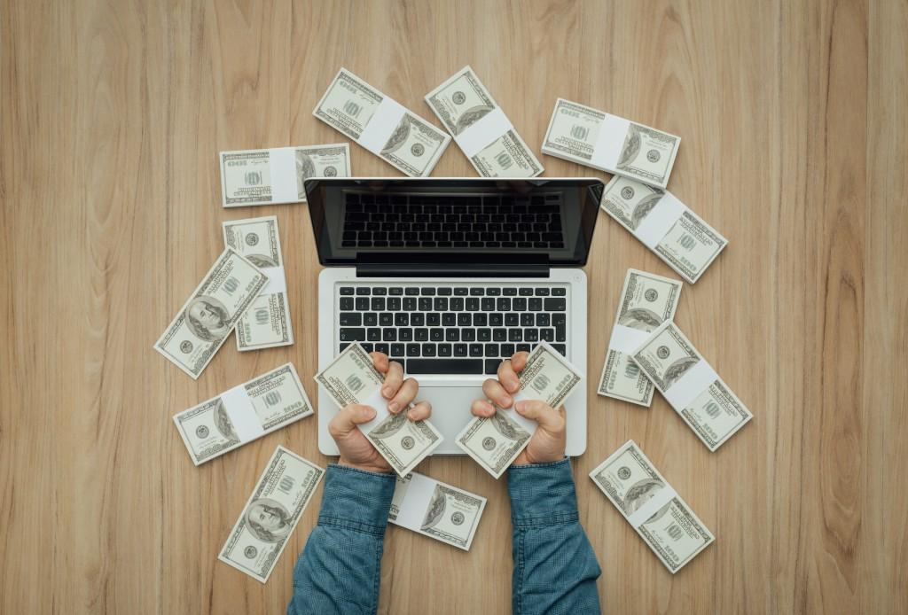 Hands Holding Bundle of Cash