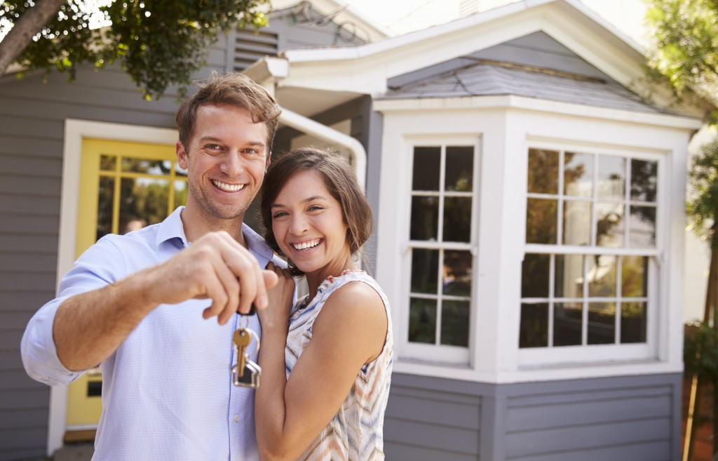 a couple holding their key to their new house