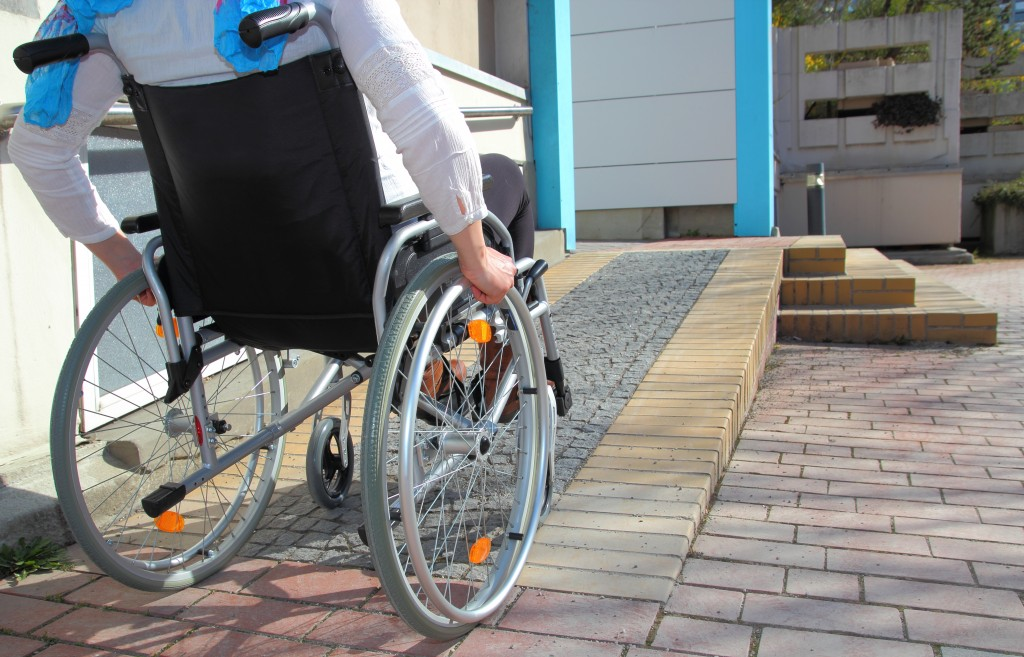 man in his wheelchair going up the disabled ramp