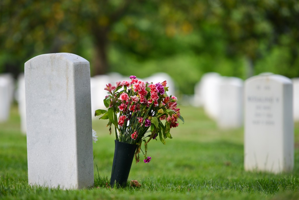 photo of a tomb with bouquet of flowers beside it
