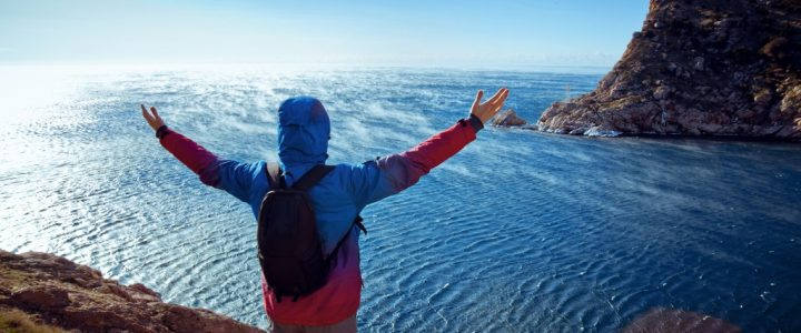 a man on top of the mountain raising his both hands in front of the sea