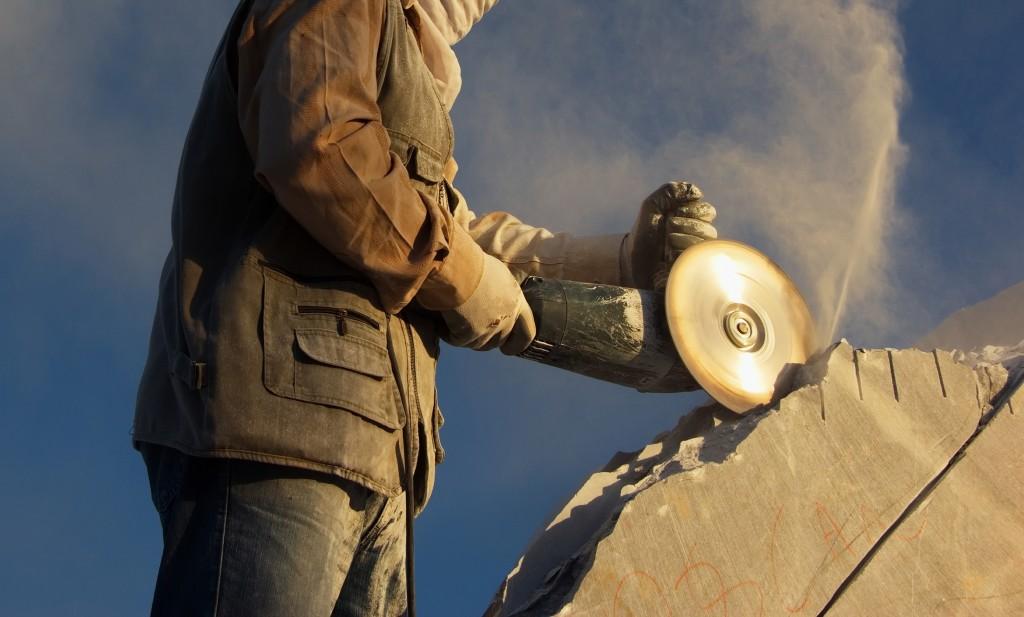 Stone mason cutting a stone