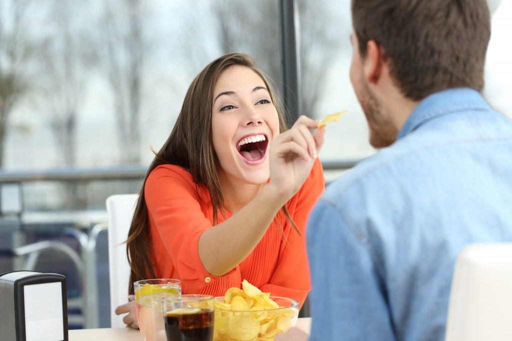 Woman giving her boyfriend some potato chips