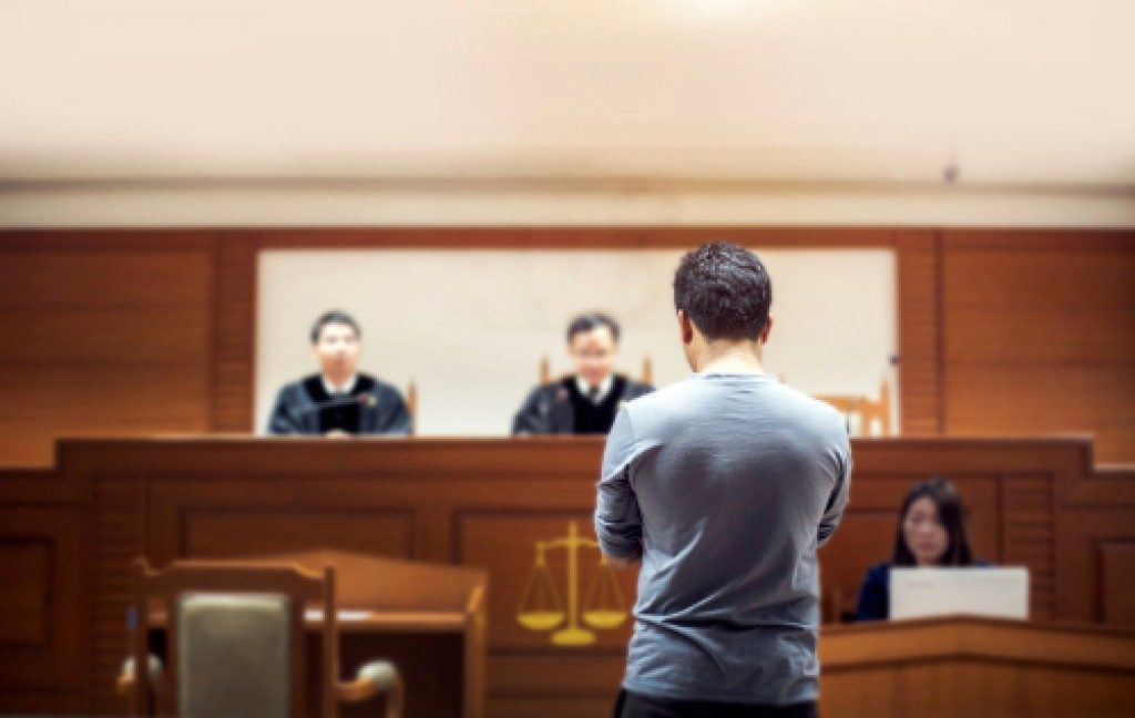 person in front of judges at the courtroom