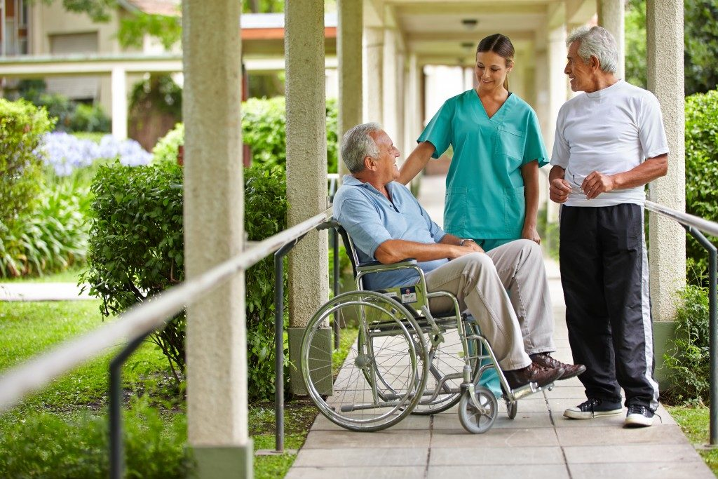 Two senior citizens talking to a nurse