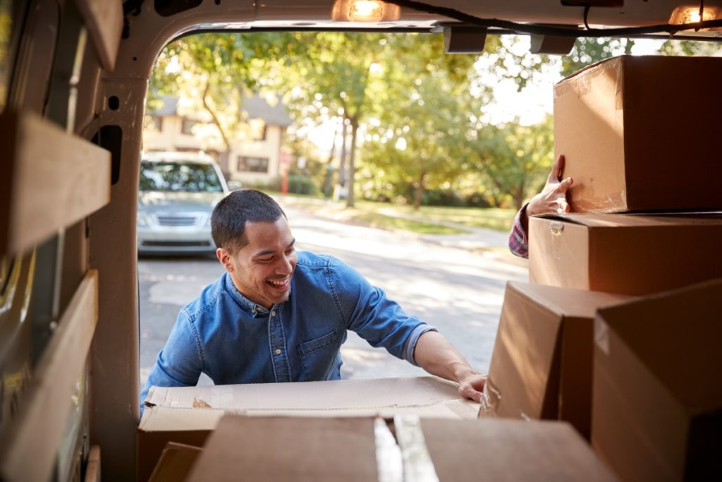 Man packing his boxed items into a vehicle