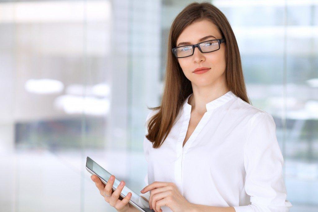 woman wearing glasses holding an ipad