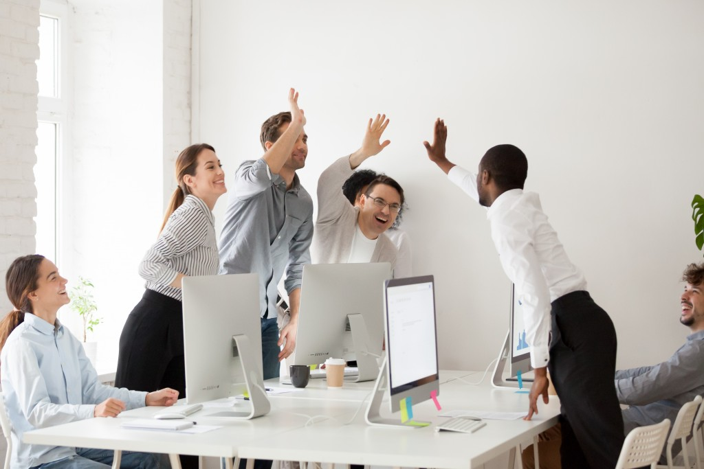 happy employees giving high five to each other