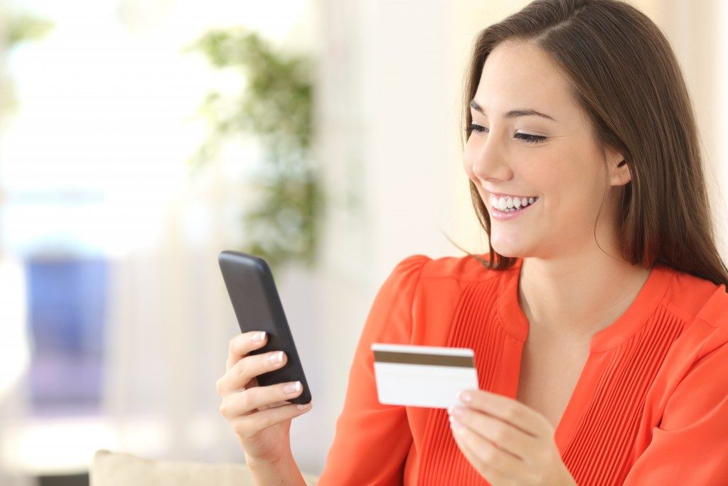 woman purchasing online while holding credit card