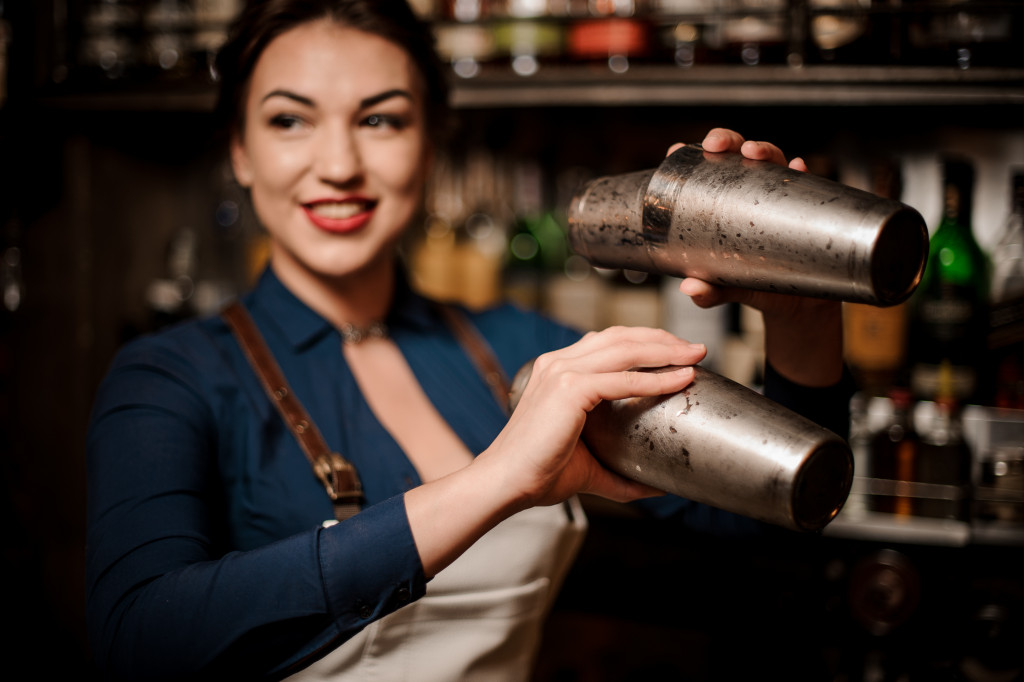Bartender in the white apron holding in her hands two steel cocktail shakers at the bar counter